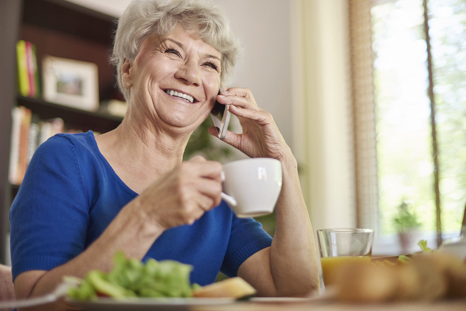 Mature lady on telephone with cup of tea